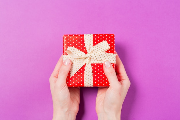 Close-up of woman hands holding gift present box on purple background. holiday valentine's day