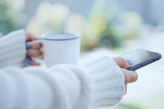 Close up woman hands holding hot cup of coffee or tea and using smartphone in cold weather background, wearing warm fur knitted clothes