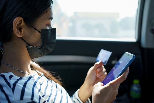 Закройте вверх руки женщины держа смартфон и кредитную карту, сидя на заднем сиденье автомобиля.