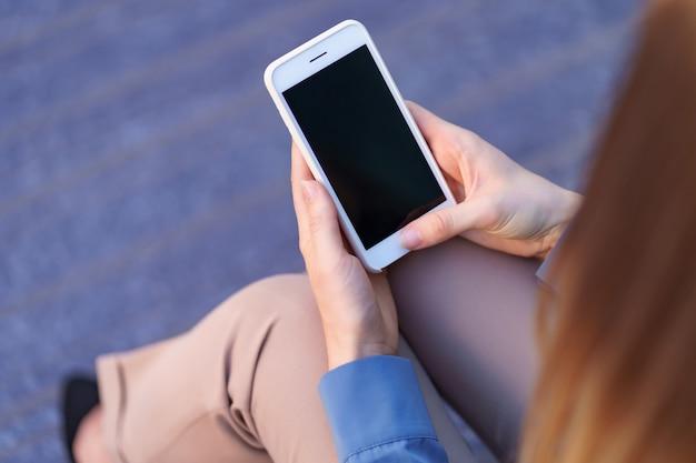 Закройте вверх руки женщины, держа смартфон с черным экраном