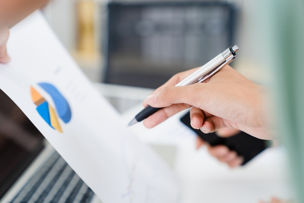 Close up woman hands pointing pen at business data chart paper for business information explanation