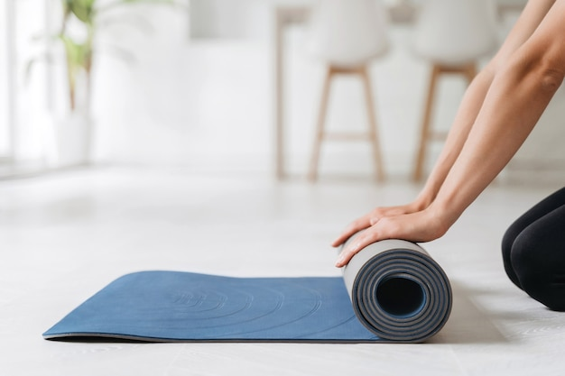 Close up of woman hands prepairing fitness mat for yoga or workout