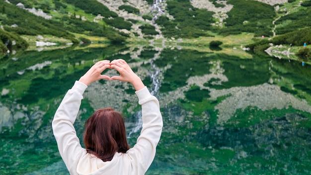놀라운 폭포와 복사 공간이있는 호수의 투명하고 깨끗한 물에 마음을 보여주는 여자 손을 닫습니다. 산 개념의 직업. 자연과의 고독.