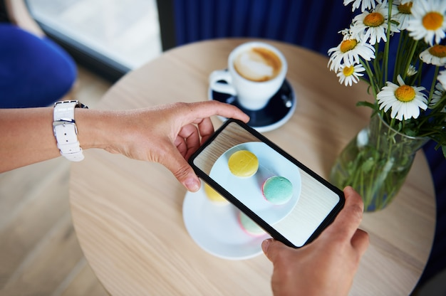 Close-up of woman hands taking a photo of plate with macarons on a wooden table in cafeteria. coffee break time. mobile phone in live view mode