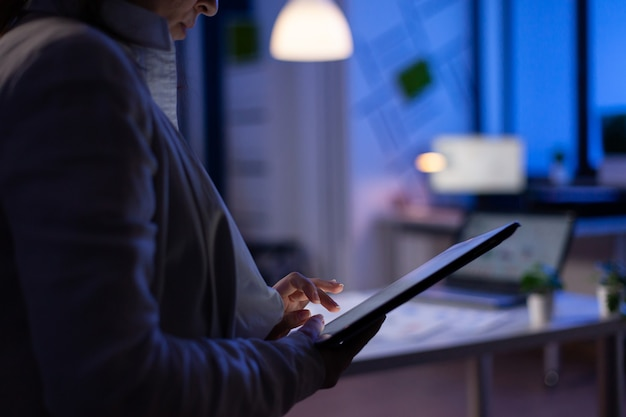 Close-up of woman hands typing on tablet checking financial graphs standing in start-up office late at night