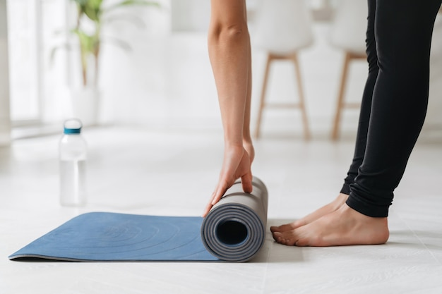 Close up woman hands unrolling mat preparing for fitness workout or yoga at home