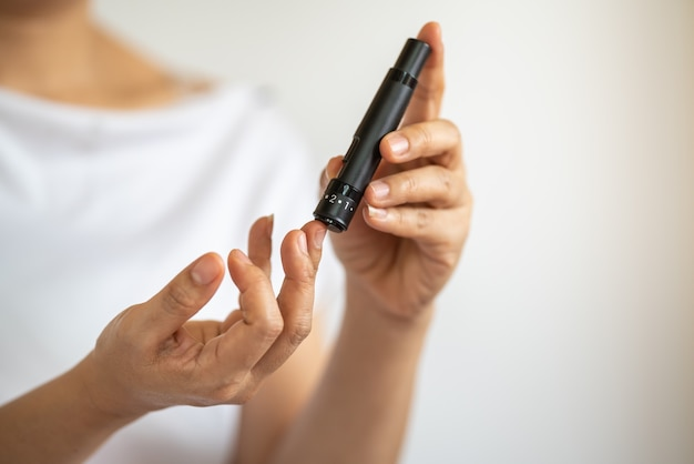 Close up of woman hands using lancet on finger to check blood sugar level