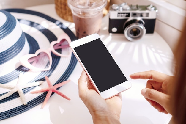 Close up woman hands using smart phone on white table, travel concept. flat lay, copy space
