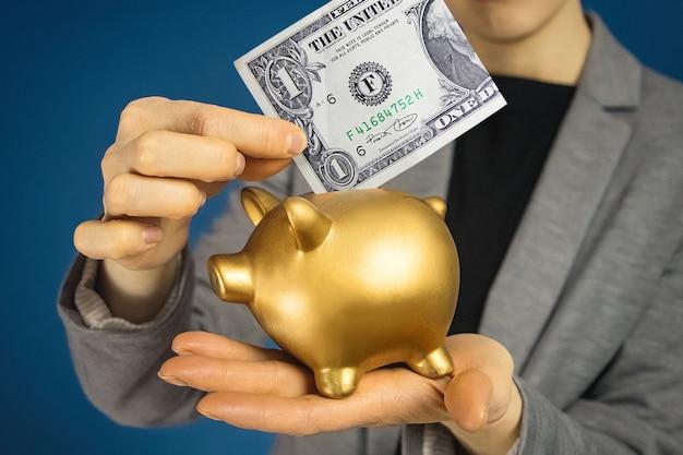 Руки женщины конца-вверх с американским долларом и копилкой.