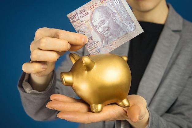 Руки женщины конца-вверх с индийской рупией и копилкой.