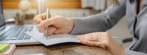 Крупным планом женщина руки писать в газете на офисном столе рядом с ноутбуком