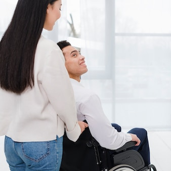 Close-up of a woman helping disabled woman on wheelchair