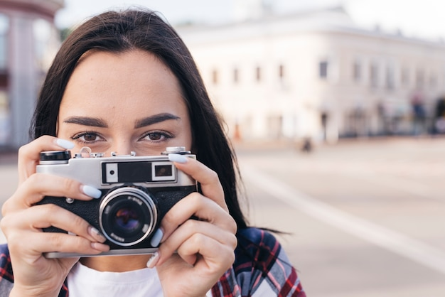 Close-up of woman hiding mouth with holding retro camera