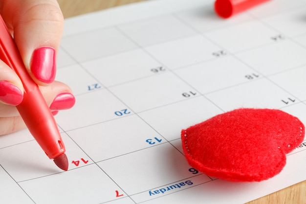 Close-up of woman highlighting date on calendar