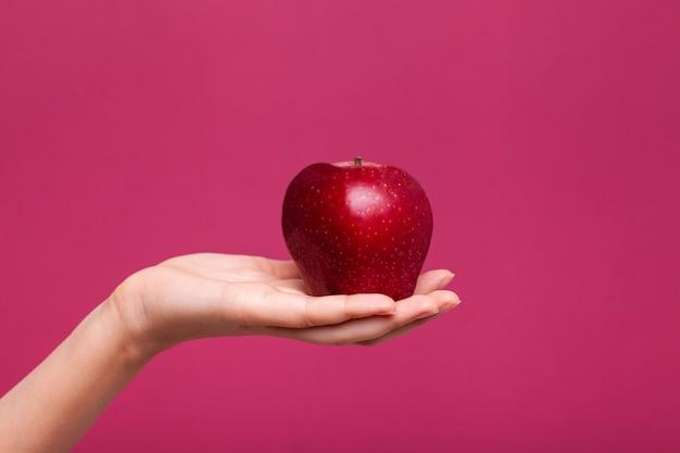 Крупным планом женщина держит в руке свежее яблоко