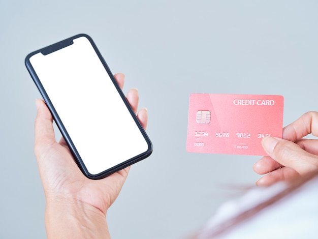 Close-up of woman hold mobile phone, blank screen and credit bank card on gray background