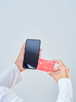 Close-up of woman hold smartphone, blank screen and credit bank card on gray background