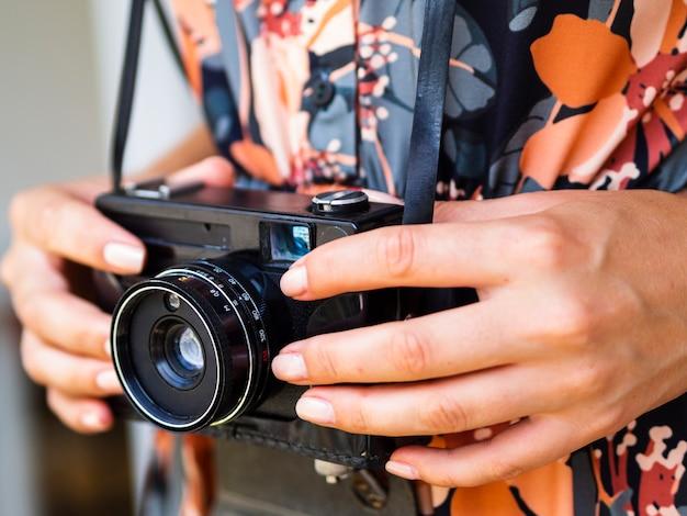 レトロな写真カメラを保持しているクローズアップの女性