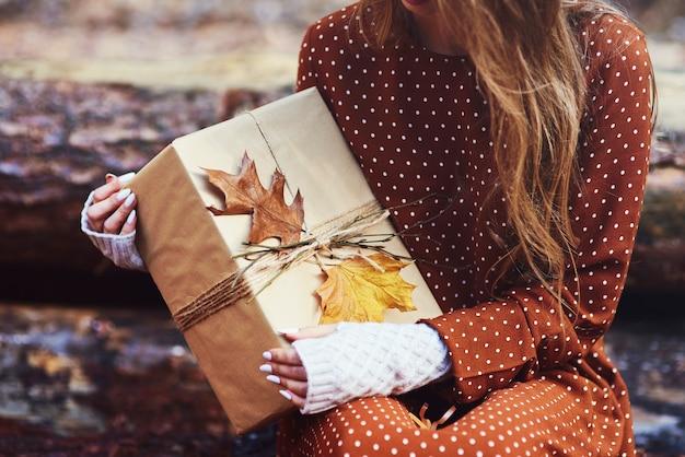 Primo piano di una donna che tiene un regalo incartato autunnale