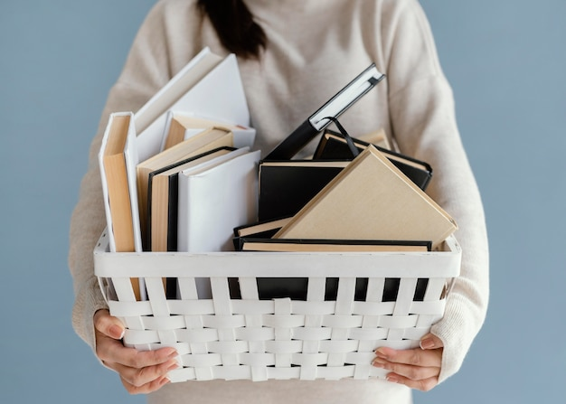 Close up woman holding basket with books