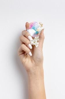 Крупным планом женщина, держащая красивый кристалл и цветок