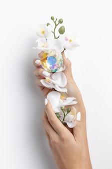 Женщина конца-вверх держа красивый цветок и кристалл