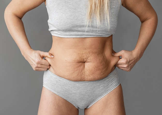 Close up woman holding belly fat