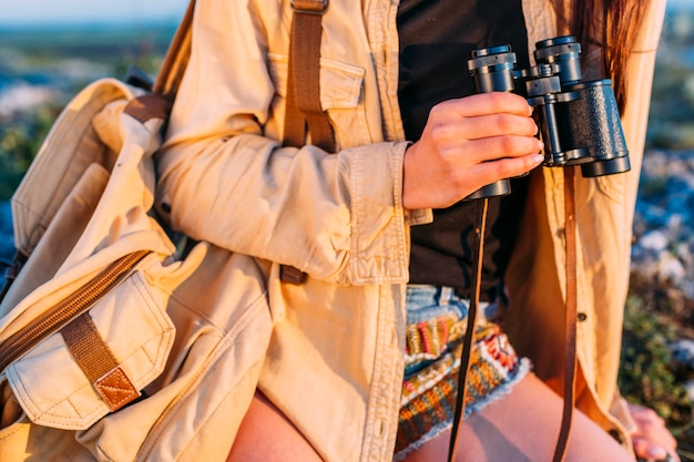 Close-up of a woman holding binocular