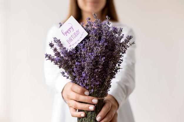 誕生日のラベンダーの花束を保持している女性をクローズアップ