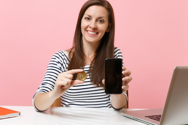 Close up of woman holding bitcoin metal coin of golden color, future currency and mobile phone with blank empty screen sit at desk isolated on pink background. achievement business career. copy space.