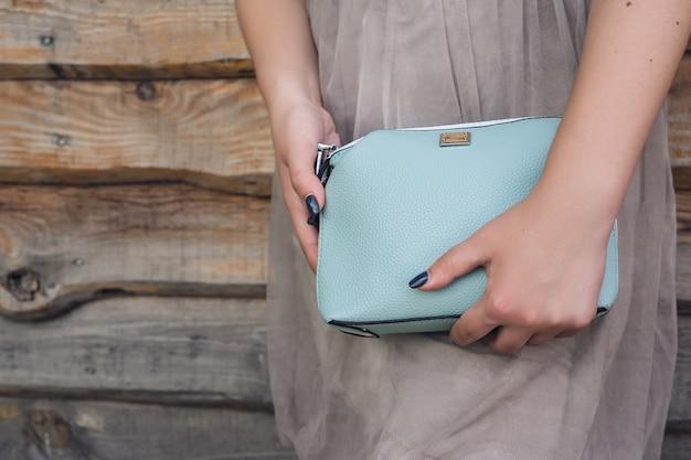 Close up woman holding blue handbag on wooden background