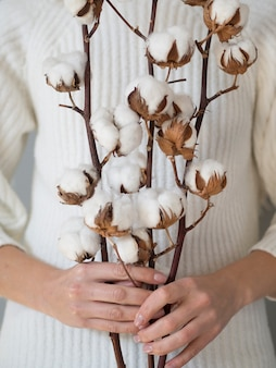 Close-up woman holding branches with cotton flowers