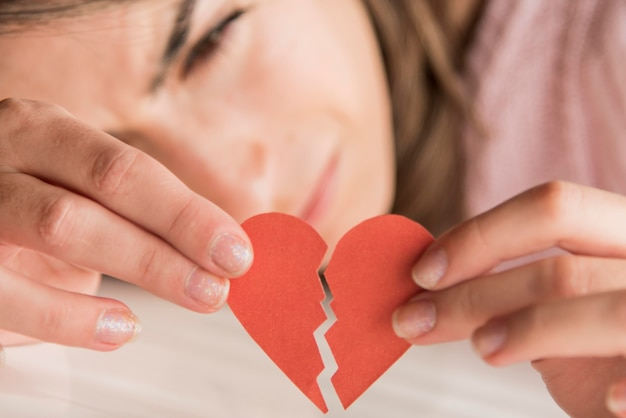 Close-up woman holding broken heart