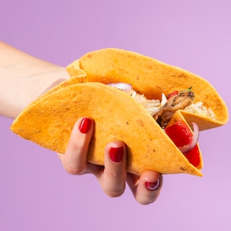 Close-up woman holding burrito with purple background