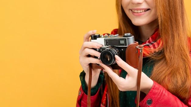 カメラを保持しているクローズアップの女性