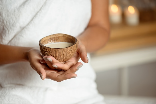 Close up of woman holding coconut in spa salon.