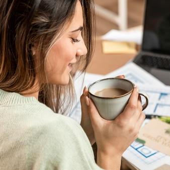 コーヒーカップを保持しているクローズアップの女性
