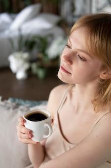 Primo piano donna che tiene una tazza di caffè