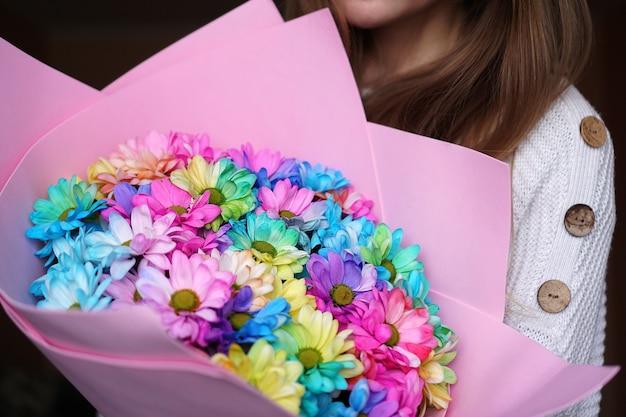 クローズアップ-ピンクのパッケージでカラフルなレインボーブーケを保持している女性