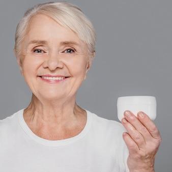 クリーム色の容器を保持しているクローズアップの女性