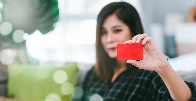 Close up woman holding credit card for shopping online at home