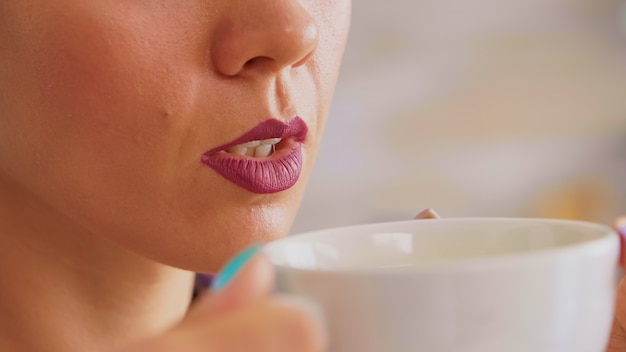 Close up of woman holding a cup of hot green tea trying to drink it. pretty lady sitting in the kitchen in the morning during breakfast time relaxing with tasty natural herbal tea from white teacup.