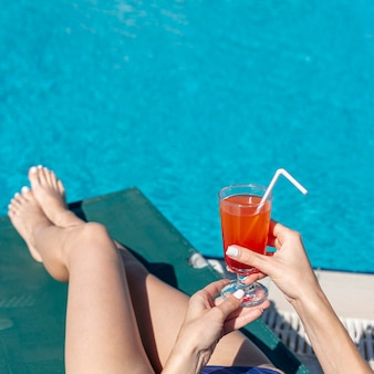 Close up woman holding drink laying on lounge
