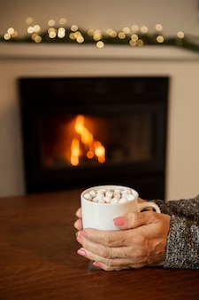 暖炉の近くの飲み物を保持しているクローズアップの女性