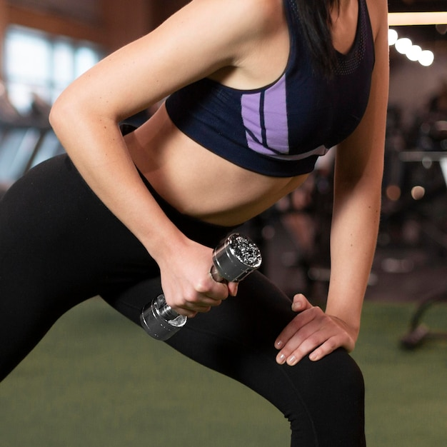 Close-up woman holding dumbbell