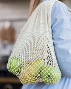Close-up woman holding eco bag with organic fruits