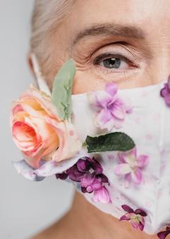 꽃 마스크를 들고 클로즈업 여자