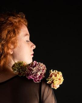 Donna del primo piano che tiene un fiore