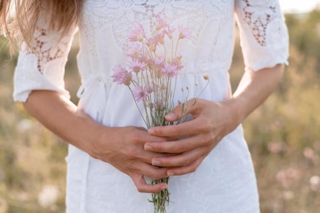 Крупным планом женщина держит букет цветов
