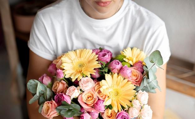 꽃 꽃다발을 들고 여자를 닫습니다